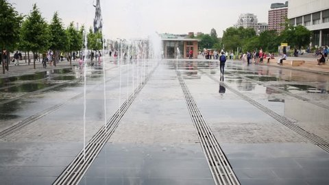 Water jets of dry fountain in area of park Muzeon and people around.