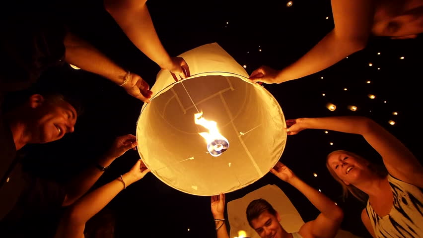 Chiang Mai, Thailand - November 16: Tourists getting ready to launch floating lantern into the night sky during Loy Krathong Festival in Chiang Mai, Thailand.