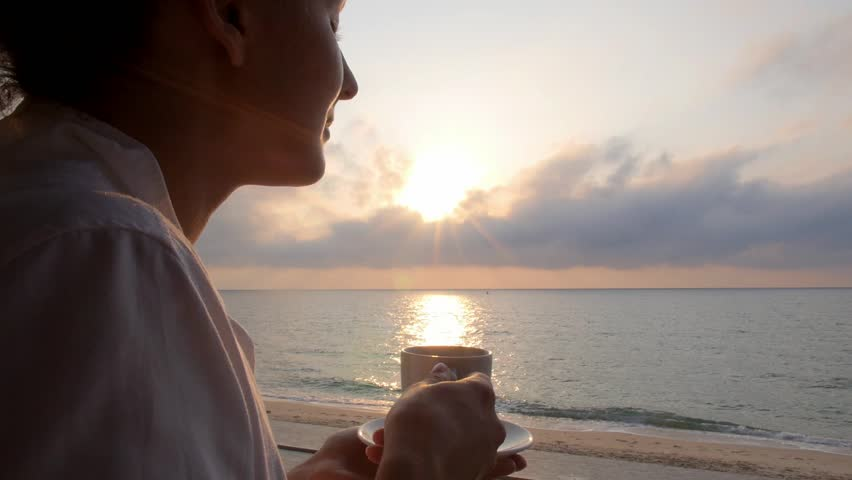 Woman Taking a Sip of Coffee in Beach Restaurant by Sea | Shutterstock HD Video #17082304