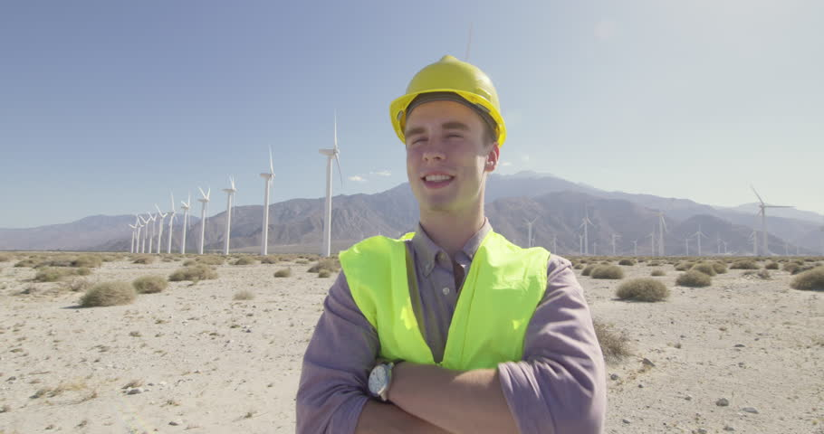 Wind farm technician in hard hat and wearing yellow high-visibility vest, looking confident and happy as camera dollies around him. Medium shot, originally recorded in 4K.