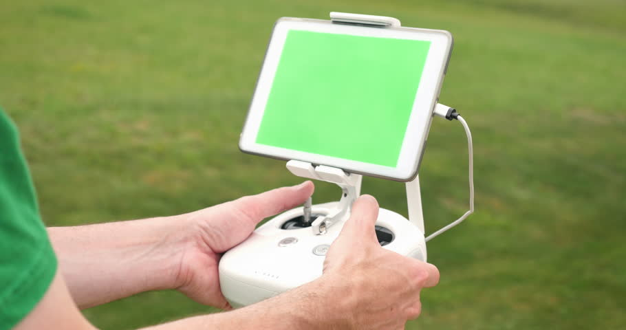 A Man Uses RC Controller For Drone Or UAV Outside In An Open Field Green Screen Generic Tablet With Optional Corner Markers Advanced