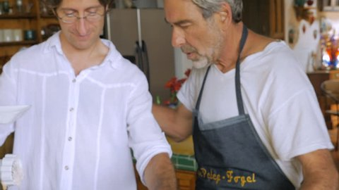 A middle aged man and older senior have fun working together grinding fish in a modern kitchen