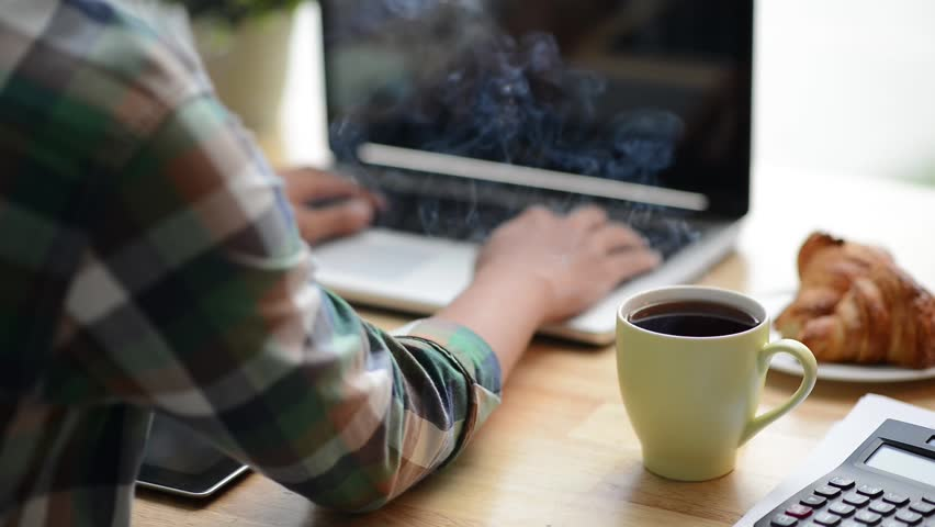 Cinemagraph of steaming coffee on desk of young programmer