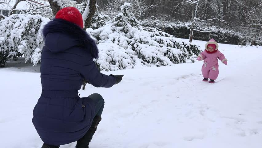 Happy baby girl walk toward mother on snow in winter season. 4K   Shutterstock HD Video #17135500