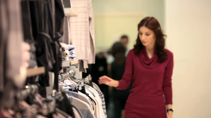 Young woman carefully picking up a shirt