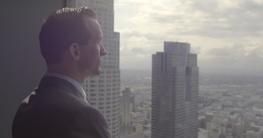 Successful young business man looks across Los Angeles from Downtown office window.  Medium close up with sunrise sky and some sunlight flare, dolly shot originally recorded in 4K