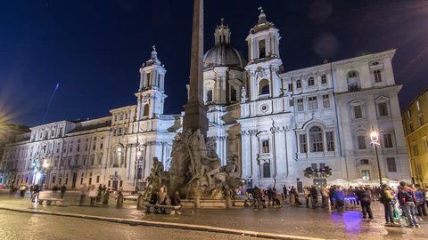 Illuminated at night the fontana of the Four Rivers timelapse hyperlapse on Piazza Navona on the Sant'Agnese in Agone church background, Rome, Italy