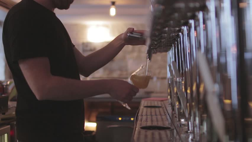 Bartender Pouring Craft Beer From Tap. Bartender pouring a perfect draft beer and serving client.