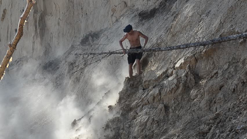A man climbs a cliff and sways the trees in the dust. | Shutterstock HD Video #17246710