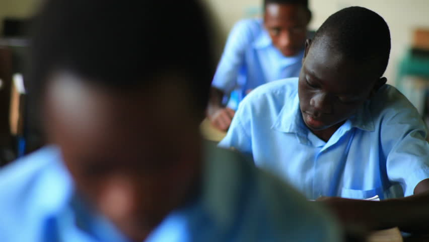 KENYA, AFRICA - CIRCA 2011: Shot of a school boy reading his book in class, then