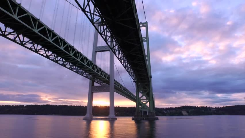 Aerial flight under the Narrows Bridge in 4k. Busy car traffic travels over the suspension bridge of the Puget Sound in Washington state | Shutterstock HD Video #17262367