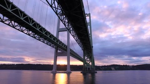 Aerial flight under the Narrows Bridge in 4k. Busy car traffic travels over the suspension bridge of the Puget Sound in Washington state