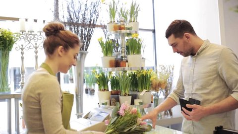 people, shopping, sale, floristry and consumerism concept - happy florist woman counting bunch cost at cashbox and man with credit card paying for purchase at flower shop