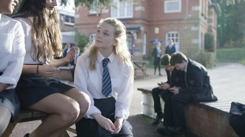 4K School girls chatting together outdoors in school playground. Shot on RED Epic. UK - April, 2016