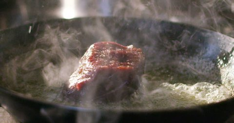 A young expert cook a beef fillet in the pan in the Italian tradition of the italian meat fillet gourmet beef
