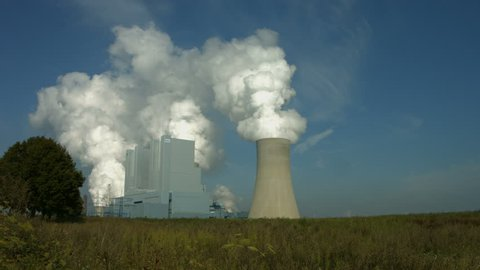Establishing shot of a huge lignite fired power plant with tall and dirty chimneys and steaming cooling towers.