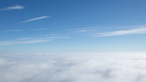 4K time lapse high angle view of approaching wispy clouds and blue sky above the top of an inversion cloud level on a bright sunny day