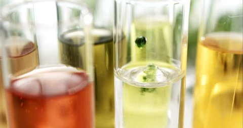 laboratory particles of vitamins or other floating particles drops in the liquid in slow motion while vitamins  come together to create a recipe for healthy skin or perfume in the laboratory
