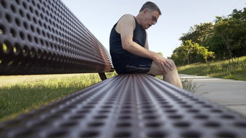 Middle aged Caucasian man with knee pain rests on a jogging path bench during outdoor exercise effort 4k
