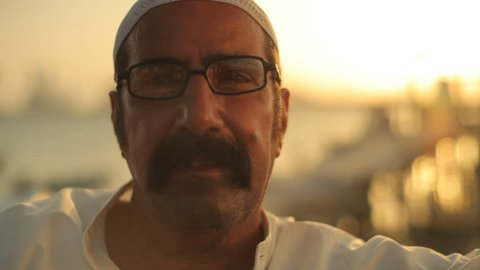 Bahrain - circa 2011 - CU handheld portrait of a Bahraini man sitting by the seaside at sunset. The Bahraini flag, the Sheikh Isa Causeway bridge and the towers of Manama are in the background.