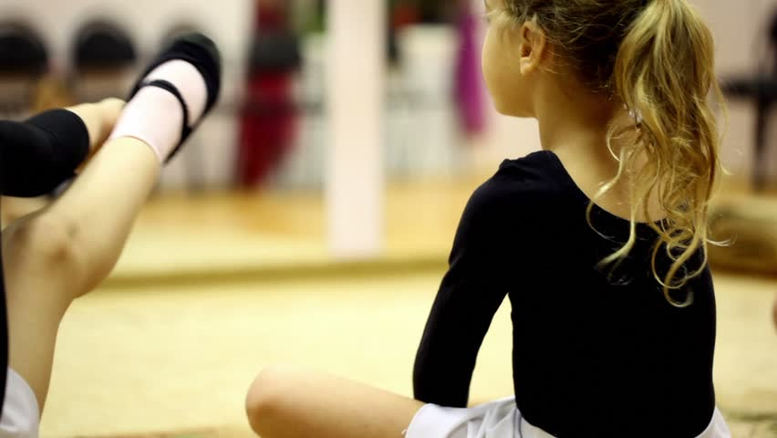 Little girl dressed in ballet clothes sit on floor and stretches risen leg, view from behind