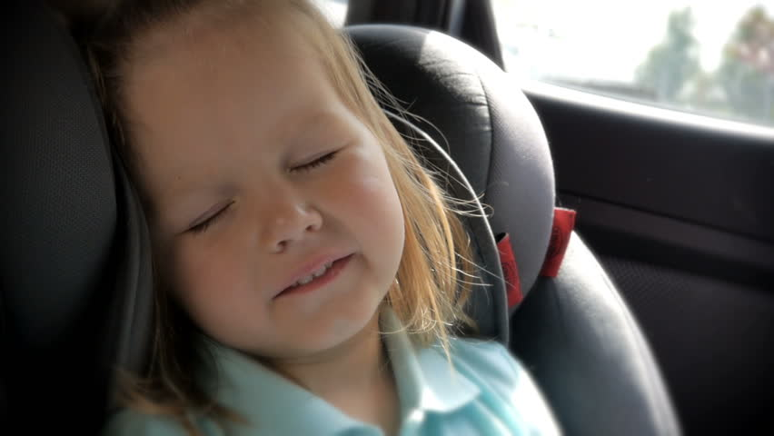 Beautiful baby girl sleeping in car seat