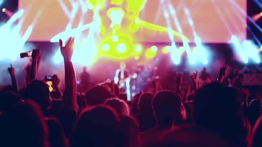 Iconic night rock concert front row crowd cheering slomo 50p.Slow motion shots from a night rock concert.People cheer move lift and clap their hands in unison against the strobing stage lights. | Shutterstock HD Video #17430547