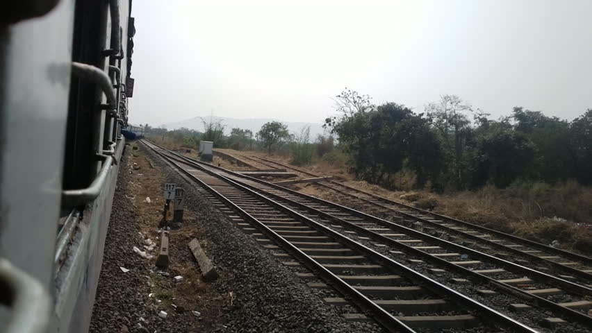 Indian Railways. Passenger train, by rail. Shot from window of last car on turning tracks. Train goes area of bushes (Kerala), train ride. Indian trains no glass in window but grates against monkeys