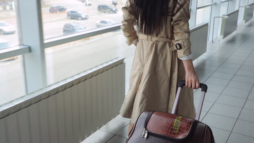 Lady in beige coat with black hair carries suitcase | Shutterstock HD Video #17442157