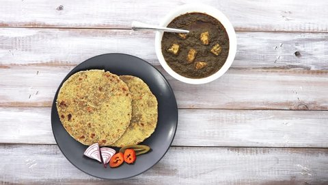 Flat lay of Gujarati flatbread Methi Thepla Indian cuisine served with traditional Punjabi Palak Paneer dish and Samosa.India food background and texture copy space