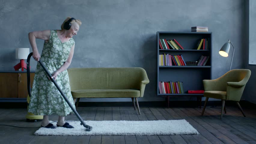 Happy elderly woman listening music on headphones and dancing with a vacuum cleaner, home fun