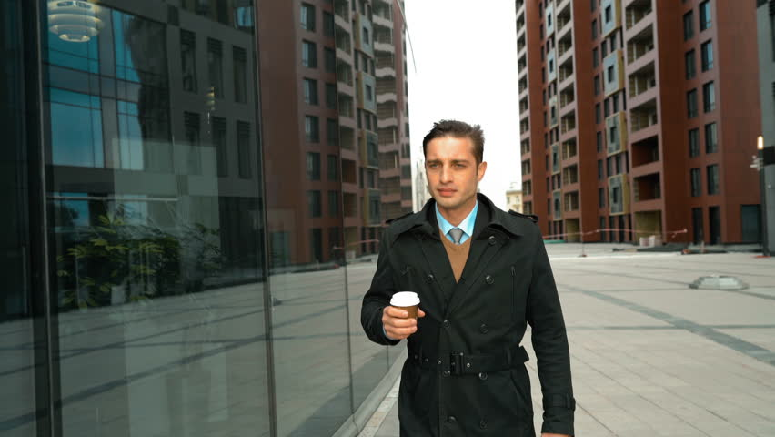Young successful businessman walking with plastic glass coffee in suit and cloak. He looking at his reflection at window with smiling. Modern glass business centre building at the background. Teal and #17526187
