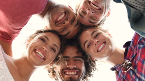 Directly below shot of young friends forming huddle. Low angle view of girls and guys with their head forming a circle. Portrait of young people looking at camera. Friendship and unity concept.