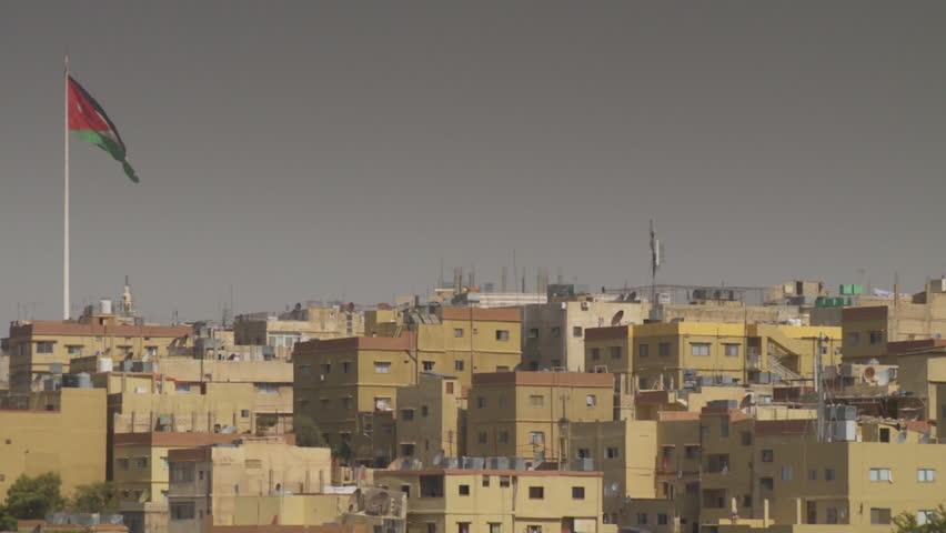 Amman, Jordan. CU pan-left across houses clustered on one of the hilltops of Amman. The Jordanian flag is flying on the horizon. (Amman, Jordan - 2016)