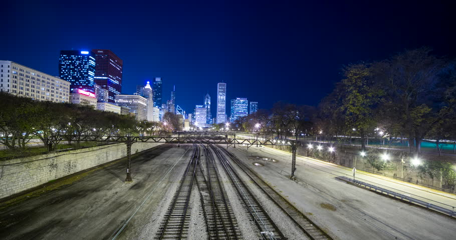 Chicago, Illinois, USA - rails and the Chicago L / Elevated near Millennium Park with illuminated Skyline in the background at night - Timelapse without motion - October 2014