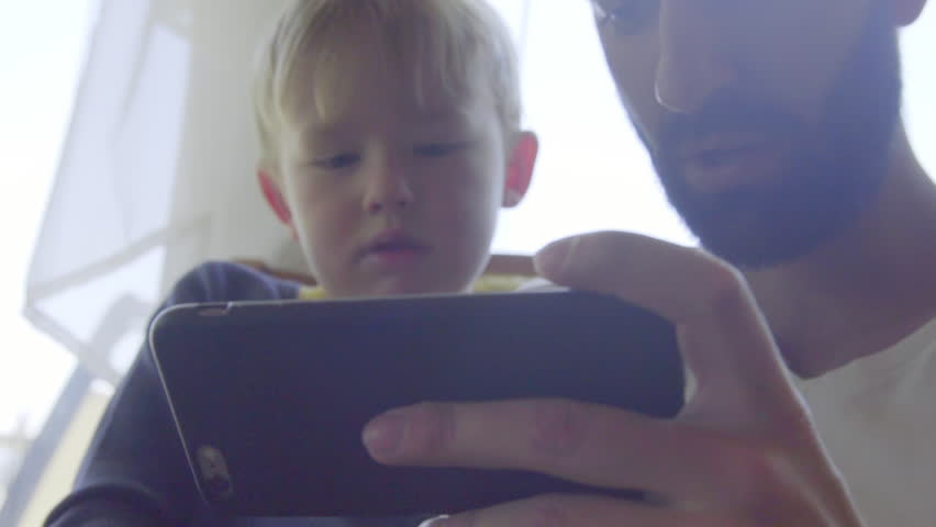 Close up shot of nephew and uncle playing games on a cell phone