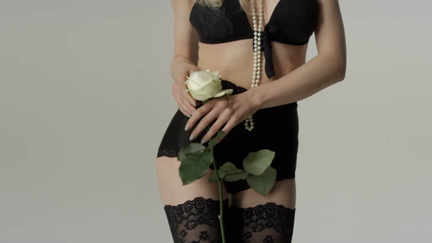 Unrecognizable sexy woman wearing lingerie posing with white rose in studio over gray background.