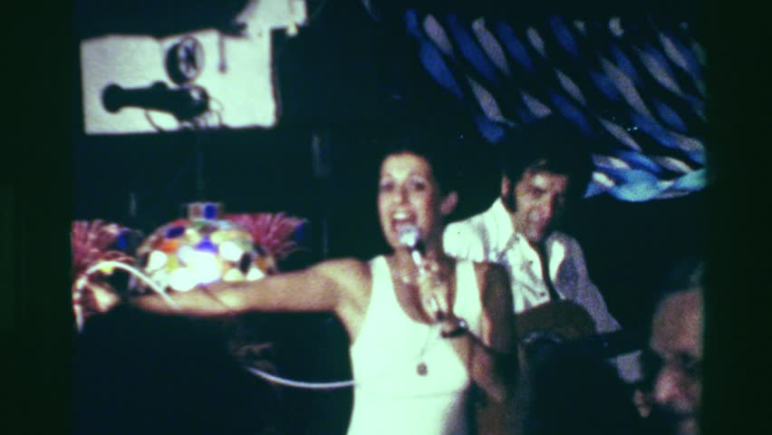 ACAPULCO, MEXICO 1978: Disco nightclub singer dancing crowd cheering drunk old people.