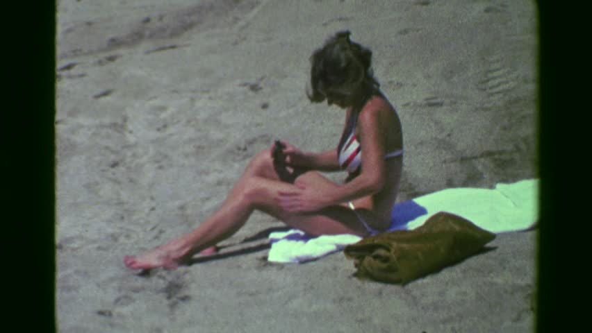 ACAPULCO, MEXICO 1978: Sexy bikini woman applying suntan lotion on legs beach sand towel.