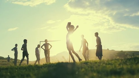 Unidentified children play football in a village on the background of sunset. Slow motion.