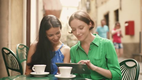 Two Attractive Young Women in Light Summer Dresses Relax and have Conversation in Street Coffee Shop. One Sharing something Exciting on her Tablet Computer with Other. Shot in 4K (UHD).