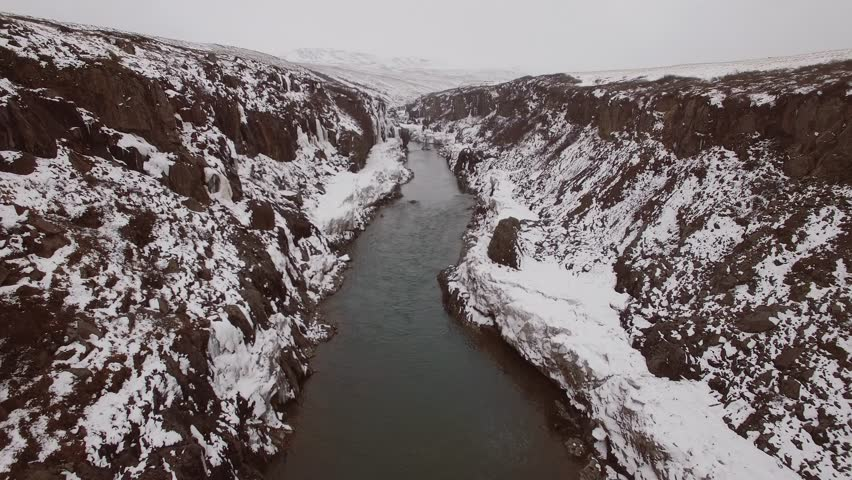 Aerial view flying through a snowy canyon and river stream in Iceland. Winter landscape. Birds flying by at end.