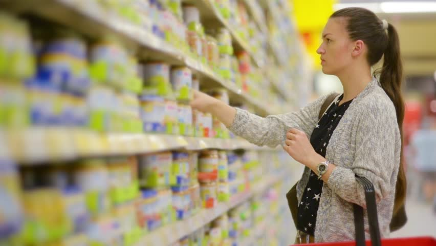 Young woman chooses baby food in the supermarket, Mother chooses food for their child in the market, girl stands near the supermarket shelf and selects the products | Shutterstock HD Video #17686006
