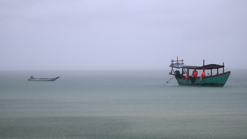 Speed boat tied up next to a traditional boat out off the coast on a rainy day ( close up ) #17686963