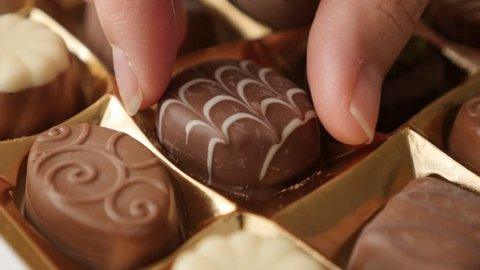 Box of chocolates choosing one with hand slow tilt 4K 2160p 30fps UltraHD footage - Hand pick gift assorted chocolate box tasty dessert background 4K 3840X2160 UHD video
