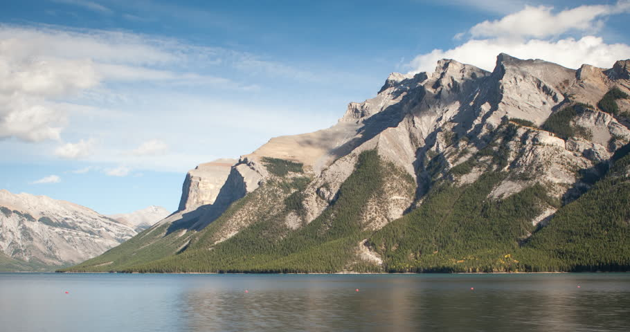 Banff National Park, Alberta, Canada - Lake Minnewanka with Mountains and forest at lakeside and clouds at blue sky - Timelapse with motion and zoom out - October 2014