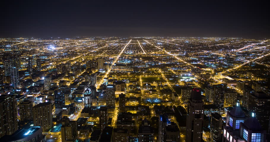 Chicago, Illinois, USA - view from the observatory of the John Hancock Center of illuminated City facing west at night - Timelapse with zoom in