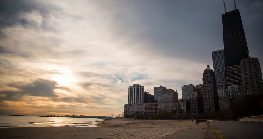 Chicago, Illinois, USA - view from the Oak Street Beach  after sunrise with clouds and colorful sky at the shore of Lake Michigan - Timelapse with zoom in - October 2014