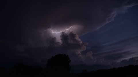 Lightning time lapse with sunset color hues in the sky at golden hour with brilliant flashes of streaking lightning playing in the beautiful clouds as the wind billows spiraling around a thunderhead.