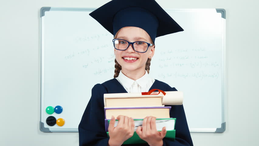 Close-up portrait student 7-8 years graduate in the mantle holding books and diploma turns at camera and laughing with teeth near whiteboard. Slider   Shutterstock HD Video #17747782